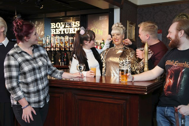 Guests taking a photo with Bet Lynch's wax figure at the rovers return in Madame Tussauds Blackpool