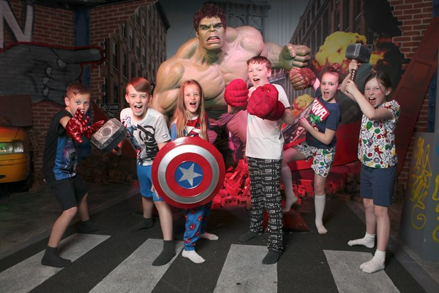 Children taking a picture next to the Hulk wax figure at Madame Tussauds Blackpool